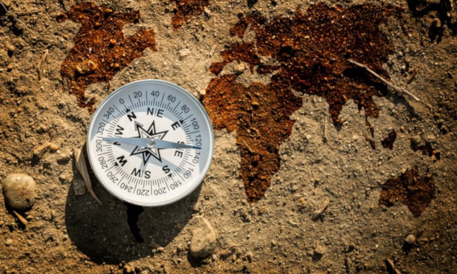 Compass on dry earth soil and world map