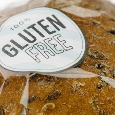 """""""100% Gluten Free"""" sticker on a loaf of brown seeded bread."""