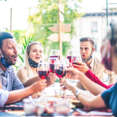 Friends toasting red wine at outdoor restaurant bar with face mask down - New normal lifestyle concept with happy people having fun together - Focus on guys behind