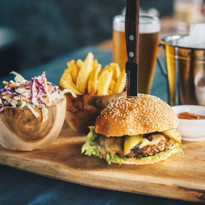 Tasty beef cheeseburger served with french fries, coleslaw salad and beer