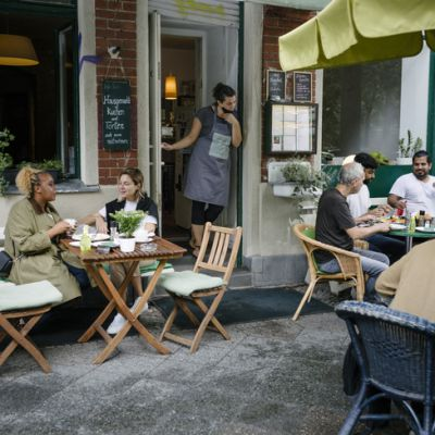 A busy restaurant facade with a waitress watching while people are sitting and eating outdoors.