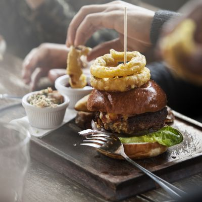Plate of burger and fries served in a pub with people snacking