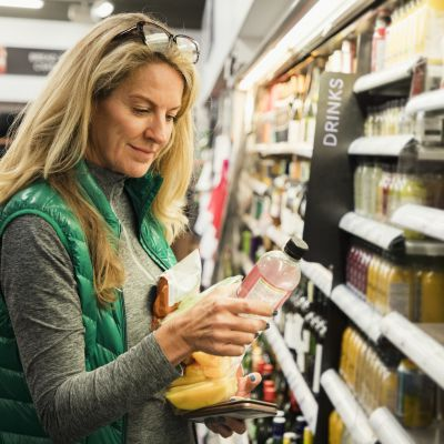A front-view shot of a mature caucasian woman standing in a supermarket, she is shopping for a healthy snack.